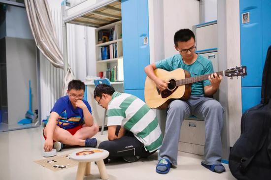 张载熙(右一)和同学在寝室娱乐,他很喜欢弹吉他(黄宇 摄)