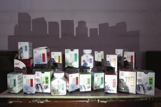 """5月31日,邵阳隆回县,田小霞服用的""""食用菌""""产品在墙上所形成的影子仿佛一座座墓碑。 金林 图"""