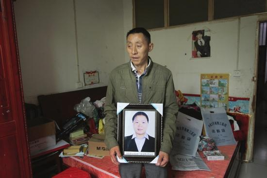 范金雄捧着妻子田小霞的遗像。 金林 图