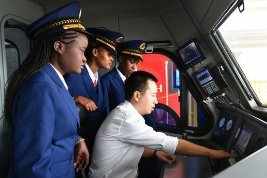2017年5月,肯尼亚女火车司机在首都内罗毕跟随中国老师熟悉操作流程。她们将驾驶由中国公司承建的蒙内铁路上的列车。经历改革开放40年,富强的中国正为世界提供更多公共产品。(孙瑞博 摄)