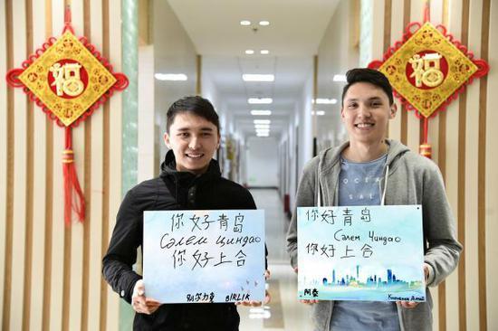 """5月3日,在青岛中国石油大学(华东)学习的哈萨克斯坦留学生别尔力克(左)和阿泰展示用中文和哈萨克文写下的""""你好,青岛""""""""你好,上合"""",表达对上合青岛峰会的期盼。(刘金海 摄)"""