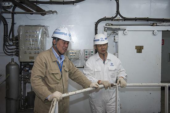 """""""天鲲号""""监造组组长王健(左一)与副组长冯长华在海试中查看运转情况。"""