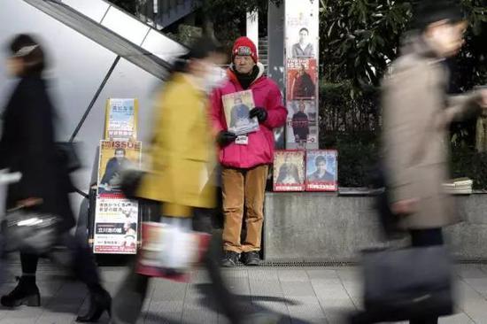 无家可归的老人在街头贩售杂志。