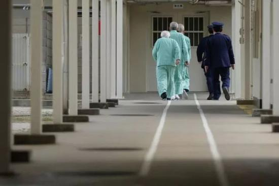 长崎佐世保监狱里,三名犯人由两名狱警护送进入监舍。图/Bloomberg