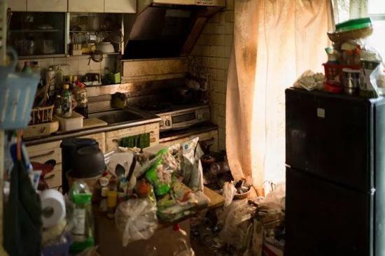 孤寡老人Kinoshita的公寓一角。房间里堆满垃圾,却摆着三四床全新的羽绒被,那是推销员利用老年孤独心理上门诈骗的杰作。Ko Sasaki摄