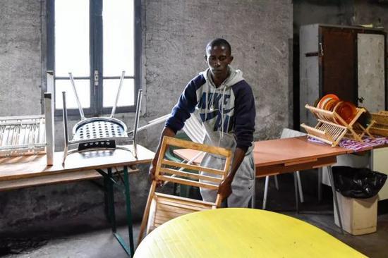 2017年9月18日,一名非法移民在法国布里昂松的一处移民临时接待中心摆放桌椅。新华社记者陈益宸摄