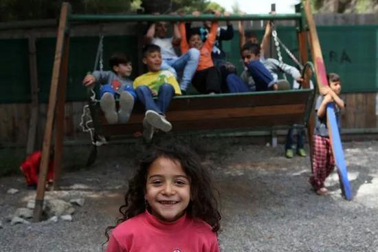 ▲资料图片:在希腊雅典以北约86公里处的里措纳难民营,儿童在秋千上玩耍。(新华社)