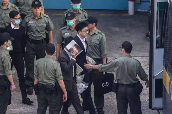 梁天琦(左三)、卢建民(左二)及黄家驹(左一)于荔枝角收押所由囚车押送至高等法院应讯。