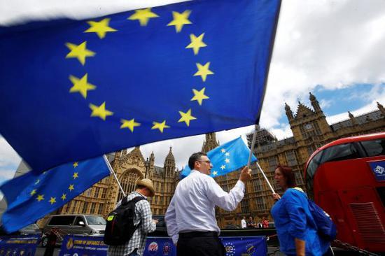 英国反对脱欧的抗议者19日在伦敦的议会大厦外挥舞欧盟旗帜(路透社)