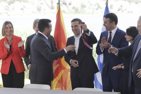 17日,在位于希腊边境普雷斯帕湖地区的普萨拉泽斯举行的签字仪式上,希腊总理齐普拉斯(中)展示马其顿总理扎埃夫(前左)赠送的领带 。(迪米特斯<span class=