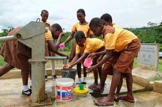 18日,加纳东部省古阿由兹村的小学生在课间休息时来到中国援建的水井打水、洗脸。(赵姝婷 摄)