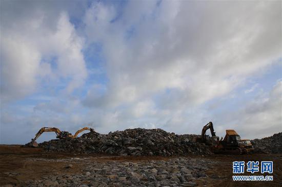 6月8日,在斯里兰卡科伦坡港口城施工现场,挖掘机对石料进行分类处理。新华社记者朱瑞卿 摄