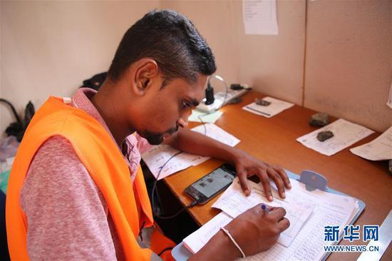 6月8日,在斯里兰卡科伦坡港口城施工现场,收料员填写单据。新华社记者朱瑞卿 摄