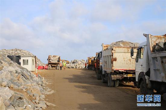 6月8日,在科伦坡港口城施工现场,载着石料的卡车陆续进场。新华社记者朱瑞卿 摄