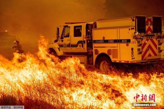 消防员在公路上奋力扑火,火势已经逼近消防车。