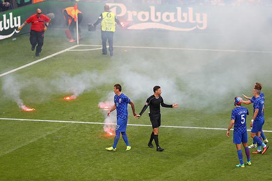 球迷向场内投掷烟花至比赛中断。 视觉中国 图