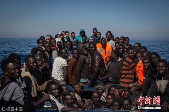當地時間2017年5月18日,意大利蘭佩杜薩,移民和難民擠在一艘小木船上等待救援。從利比亞到意大利的難民和移民人數自去年同期以來一直在上升,今年已有超過43000人記錄在案。 Chris McGrath 攝 圖片來源:視覺中國