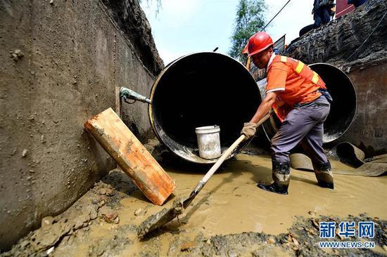 """在盛夏的高温下,这些供热管道""""医生""""们不畏酷暑,掘开路面、清理淤泥、拆除旧管、焊接新管,在泥水中摸爬滚打,用自己的辛劳保障百姓在冬季有个温暖舒适的居住环境。图为:7月15日,在长春市南关区永长路,工人高增福在地沟内清理淤泥和积水。"""