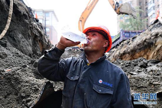 7月15日,在长春市南关区永长路,工人赵洪启在施工期间喝水解暑。