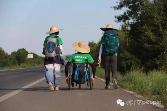 ▲2015年,雷闯和志愿者从内蒙古徒步进京,志愿者推着轮椅前行。雷闯在2016年接受新京报采访时供图。