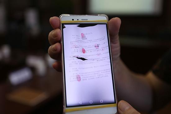 一名受害人出示套路贷的合同。视觉中国 资料