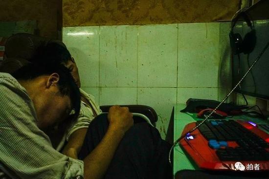 △ 网吧内,两个打工者正在座位上睡觉。他们的位置靠着厕所,很少有人选择在这里上网,是睡觉的好地方。