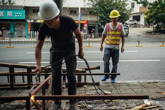 """△ 深圳坂田某街道,刘蒙的日结工作是帮助城管拆除街边的广告牌。他们这些找来的""""临时工""""因为没有技术,大多是打打杂,维持一下现场的秩序,8个小时120元钱。"""