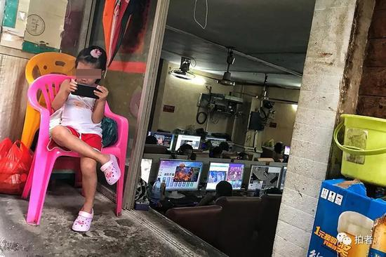 △ 三和人力市场附近的小巷中,网吧老板的孩子在门口玩手机,网吧内生意兴隆,这几天总是下雨,网吧内一位难求。