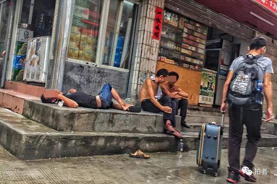 △ 下午4点,三和人力市场附近的小巷中,喝醉的打工者躺在路边,新来的打工者拖着行李从一旁走过。