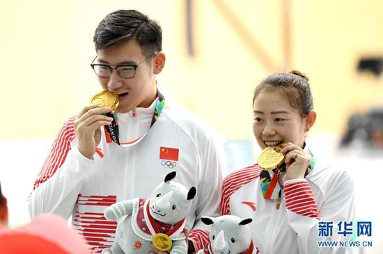 8月19日,获得冠军的中国选手纪晓晶(右)、吴嘉宇展示金牌。 当日,在第18届亚运会10米气手枪混合团体赛决赛中,中国选手纪晓晶、吴嘉宇以473.2环的成绩夺冠。 新华社记者程敏摄