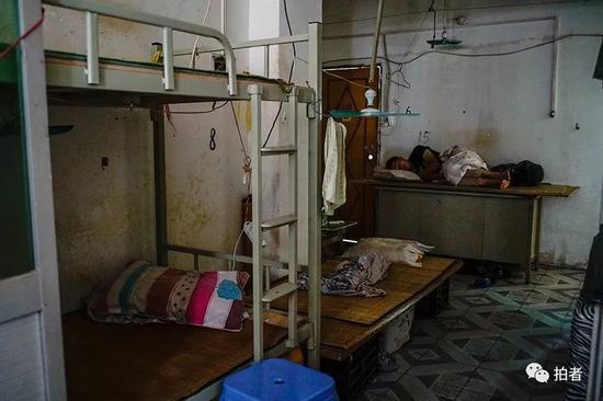 """△ 一位来三和找工作的打工者躺在桌子制成的""""床铺""""上睡觉。像这样的床铺,每个15元,布满在三和人力市场附近的窄巷中。"""