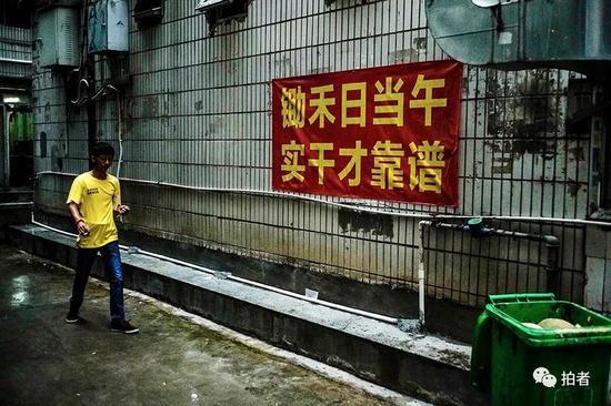 △ 早晨7点,徐家穿过窄巷,准备去找当日的工作。三和人力市场附近的窄巷中挂了许多的励志和警示标语。