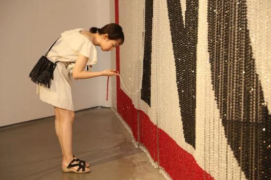 蔡雅玲的作品《No》主体是由黑、白、红三色串成的珠帘。观众从中穿过时将平静的珠帘打破,从这一由静至动的过程中获多重感官上的触动。