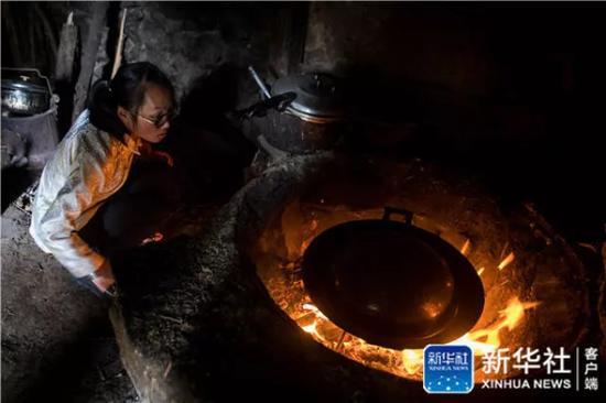 ↑在云南省曲靖市会泽县,仇文飞在家中的灶房做午饭(8月29日摄)。新华社记者 胡超 摄