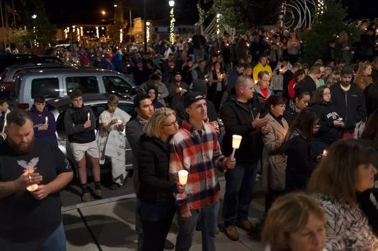 ▲周一晚,近千人聚集纽约州的一个公园,悼念20名遇难者。 图据《纽约时报》