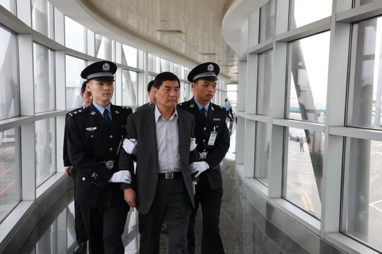 犯罪嫌疑人郑东强被押解下飞机(厦门市纪委监委 张威 摄)