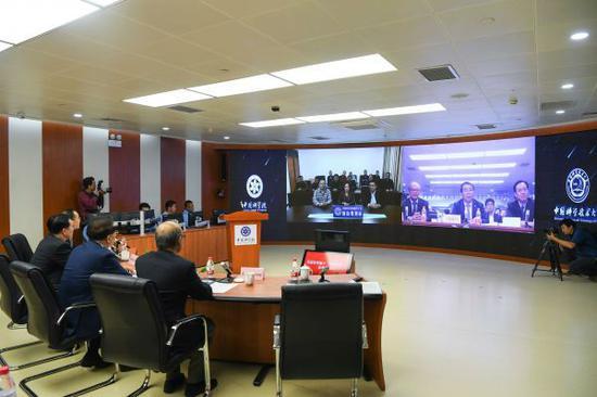 """2017年9月29日,在""""京沪干线""""北京控制中心,中国科学院院长白春礼(电子屏右侧)使用量子加密视频会议系统与中国科学院新疆天文台南山观测站的科研人员(电子屏左侧)通话。当日,世界首条量子保密通信干线——""""京沪干线""""正式开通,结合""""墨子号""""卫星,中国科学家成功与奥地利实现了世界首次洲际量子保密通信。(新华社)"""
