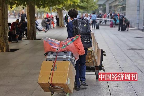 一位拖着厚重行李的旅客(《中國經濟週刊》首席攝影記者 肖翊 | 攝)