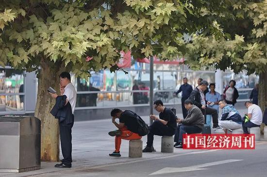 在航站樓外坐着休息的旅客(《中國經濟週刊》首席攝影記者 肖翊 | 攝)