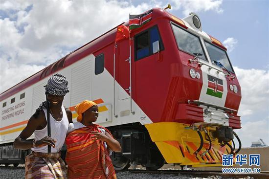 2017年1月11日,在肯尼亚蒙巴萨,当地民众在中国承制的蒙内铁路首批内燃机车旁载歌载舞。蒙内铁路是肯尼亚自独立以来最大的基础设施工程,项目累计为当地直接创造逾4.6万个工作岗位。新华社记者孙瑞博摄