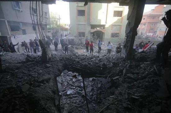 5月5日,在加沙地带拉法,巴勒斯坦人查看遭以军空袭损毁的房屋。新华社发(哈立德·奥马尔摄)
