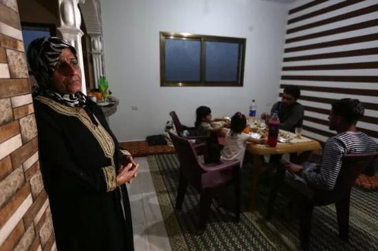 5月6日,纳吉瓦(前)和家人在亲戚家准备开斋饭。新华社发