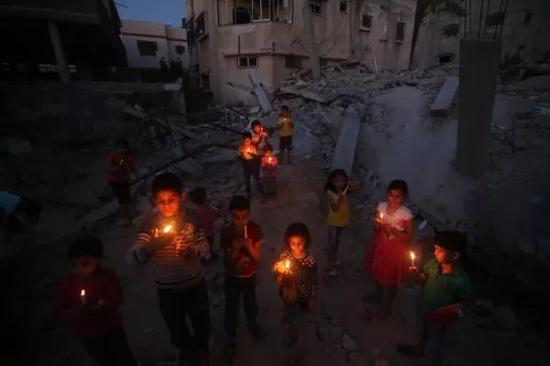 5月7日,巴勒斯坦儿童在加沙南部拉法地区一遭以色列空袭的房屋废墟上手握蜡烛祈祷。新华社发(哈立德·奥马尔摄)