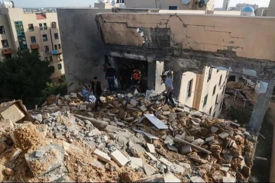 5月6日,在加沙城,巴勒斯坦人查看遭以军空袭损毁的房屋。新华社发