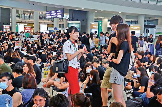 多名身穿国泰制服的空姐在机场与激进分子当中高声交谈,支持其乱港行为。(图源:大公网)