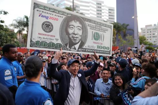 △杨安泽正在竞全集会上举着1000美圆字样的纸币(图/路透社)