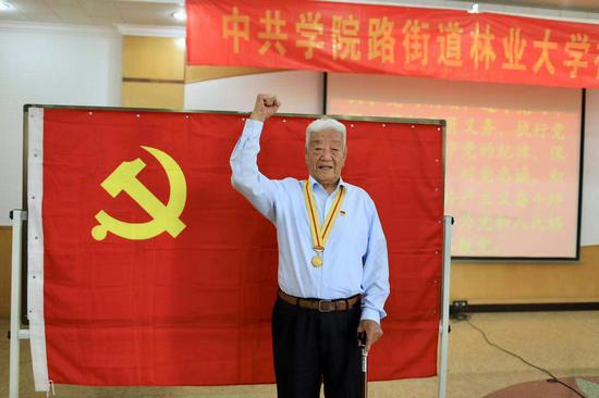 张守中老人在党旗前留影。摄影/新京报记者 浦峰