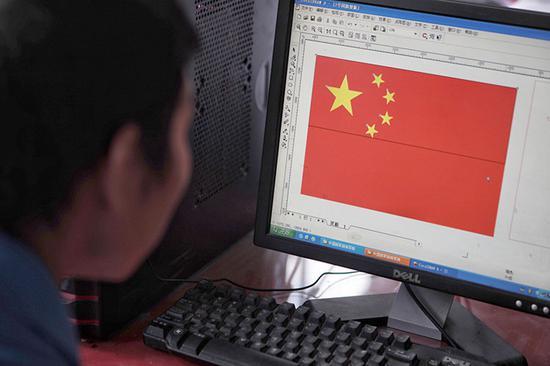 工人正在电脑上看国旗尺度电子文档。