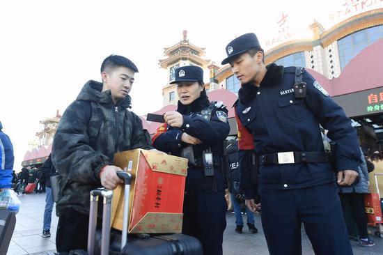 民警在核查乘客身份证信息。新京报记者 吴宁 摄