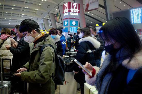 排队候车的旅客们戴着口罩,低头翻阅手机信息。